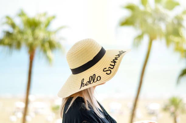 junge frauen, die einen strohhut auf dem kopf hatten, entspannen sich auf flitterwochen in einem hotelbalkon am meer. blick auf den blauen himmelshorizont und die palme. sommerei-feiertage. heller warmer filter. - hochzeitsreise zypern stock-fotos und bilder