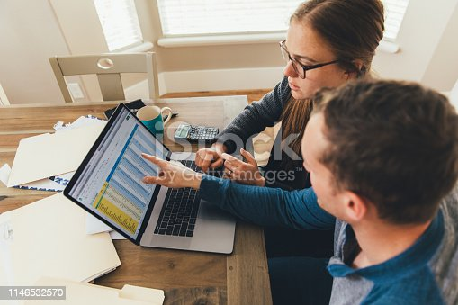 A young millennial married couple are doing their monthly budget at a kitchen dining room table in their home. They are working on their computer and phones to itemize, handle taxes, pay bills, and invest and save for the future. They are paying their bills.