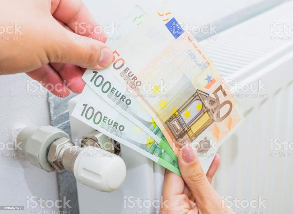 Young married couple holding cash in front of heating radiator. Payment for heating in winter. stock photo