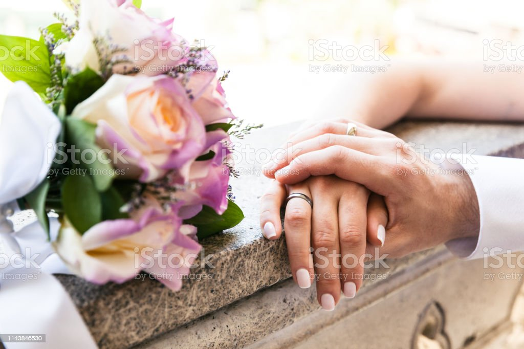 Young married couple holding hands on wedding day, love and happiness stock photo