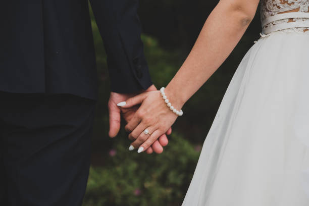 young married couple holding hands - coniugi foto e immagini stock