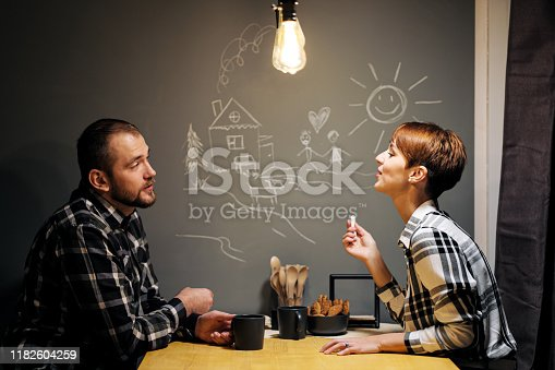 Young married couple in casual clothes, man and woman, sitting at home in the kitchen at the table. Draw their dreams with chalk on the wall. Homeliness.