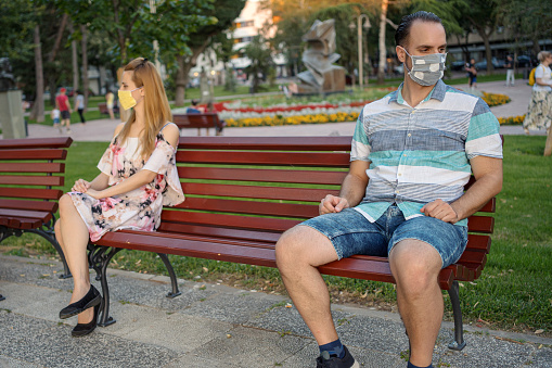 A young married couple keeps their distance with masks on their faces outdoors