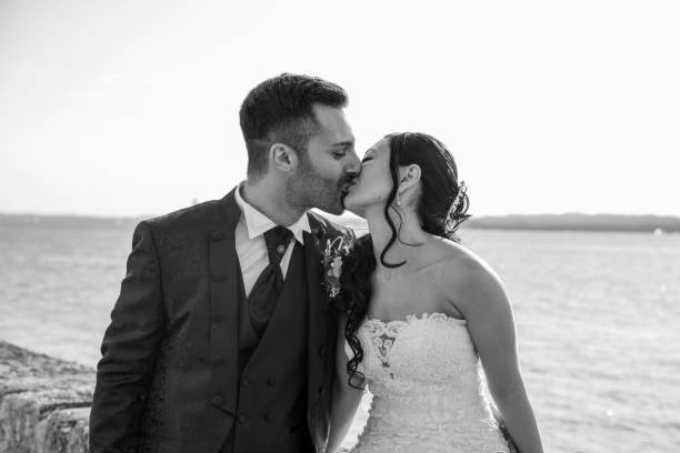Young married couple kissing each other in outdoor day in Torri del Benaco, Italy. stock photo