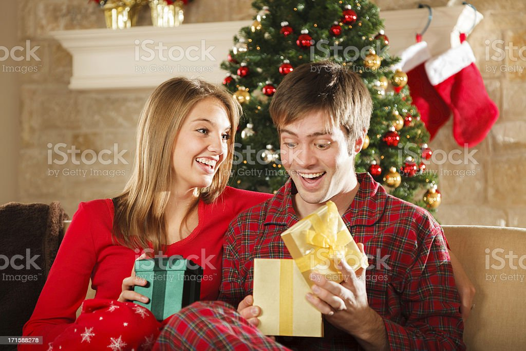 young married couple on Christmas morning opening gifts stock photo
