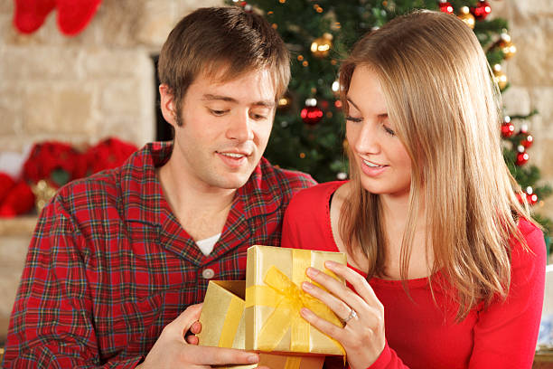young married couple on christmas morning opening gifts stock photo more pictures of 20 24 years istock