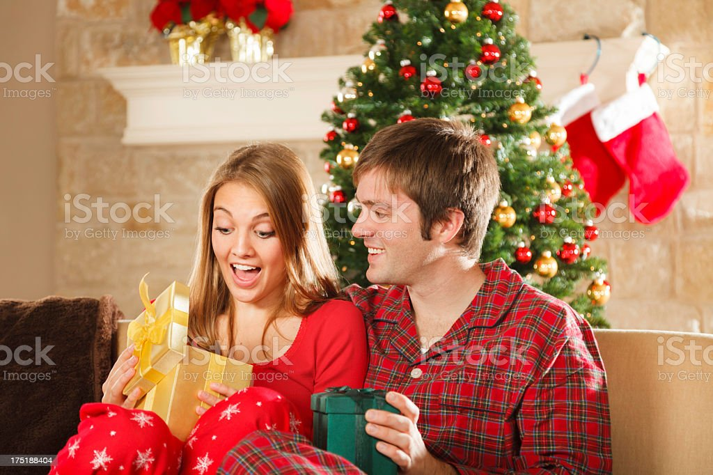 young married couple on christmas morning opening gifts royalty free stock photo