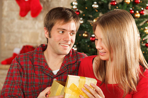 young married couple on christmas morning opening gifts stock photo 175198537 istock