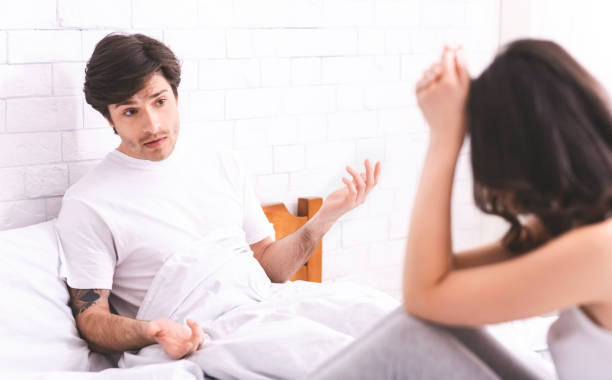 Young married couple quarreling at bed, panorama Marital misunderstanding. Young married couple quarreling at bed, panorama background of the sad couple fighting bed stock pictures, royalty-free photos & images