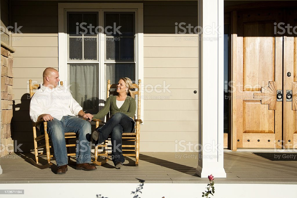 young married couple sitting on front porch stock photo