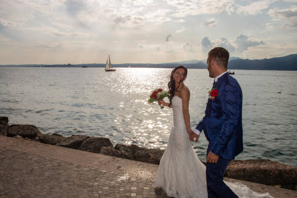 Young married couple, strolling along the lake shore in Torri del Benaco, Italy. stock photo