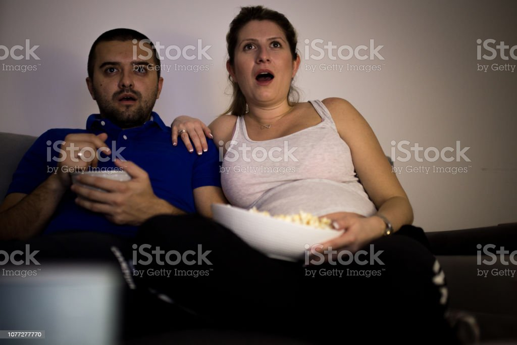 Young married couple watching exciting movie stock photo