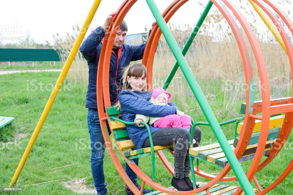 Young married couple with child in playground. Young family on a swing stock photo