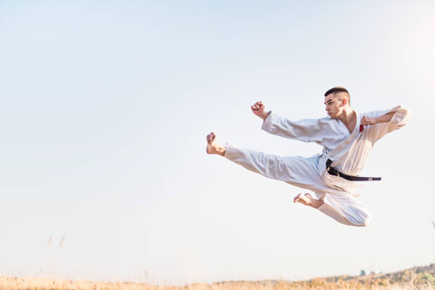 Young martial artist practicing flying kicks in nature. stock photo