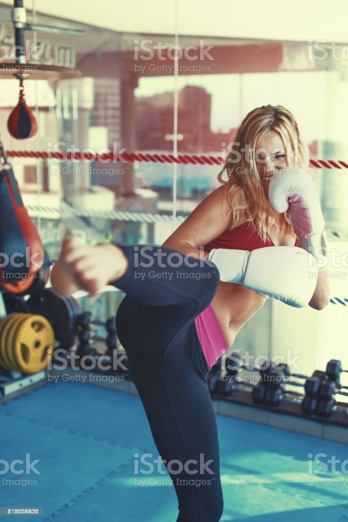 Young martial artist woman kicking in gym into camera graded stock photo