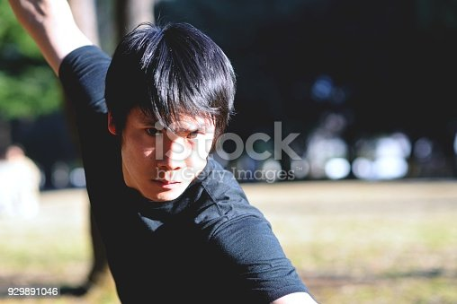 A young man practicing martial arts at a park in the late afternoon.