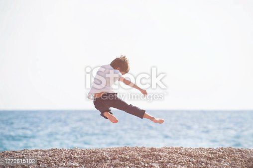 young martial kung fu kid master flying making leg kick in air during sport leisure training activity on sea beach in sunset