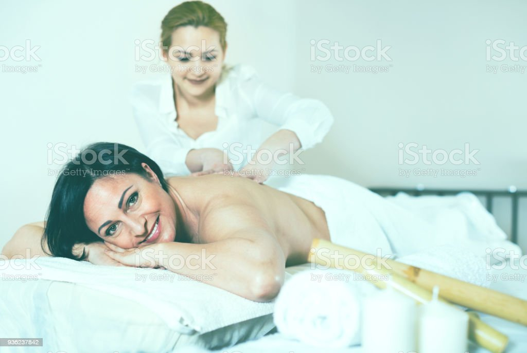 Young massagist doing shoulder massage to adult woman stock photo