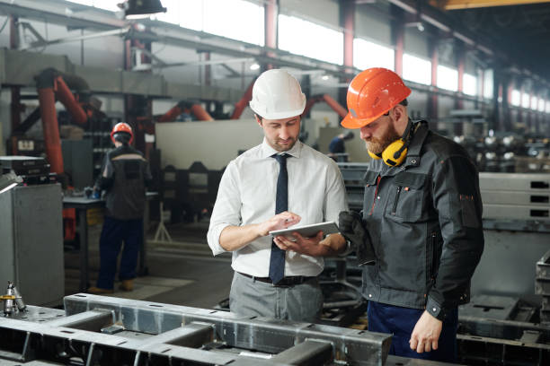 Young master in hardhat and bearded engineer discussing technical sketch Young master in hardhat and bearded engineer discussing technical sketch on display of tablet in factory workshop manufacturing stock pictures, royalty-free photos & images