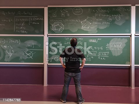 istock Young mathematician looks at formula on blackboard 1142847763