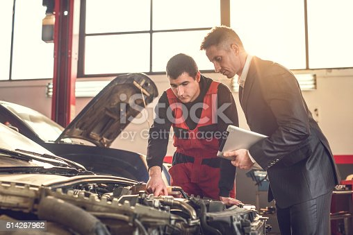 1137474295 istock photo Young mechanic and manager examining a car engine. 514267962