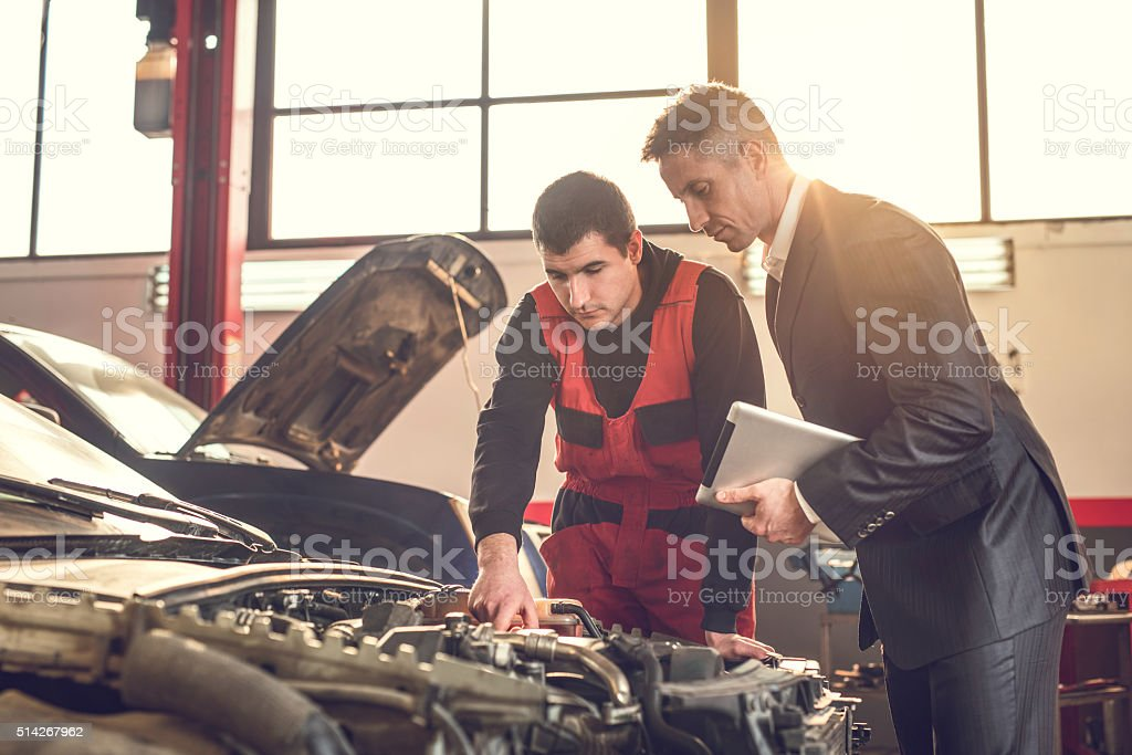 Young mechanic and manager examining a car engine. stock photo