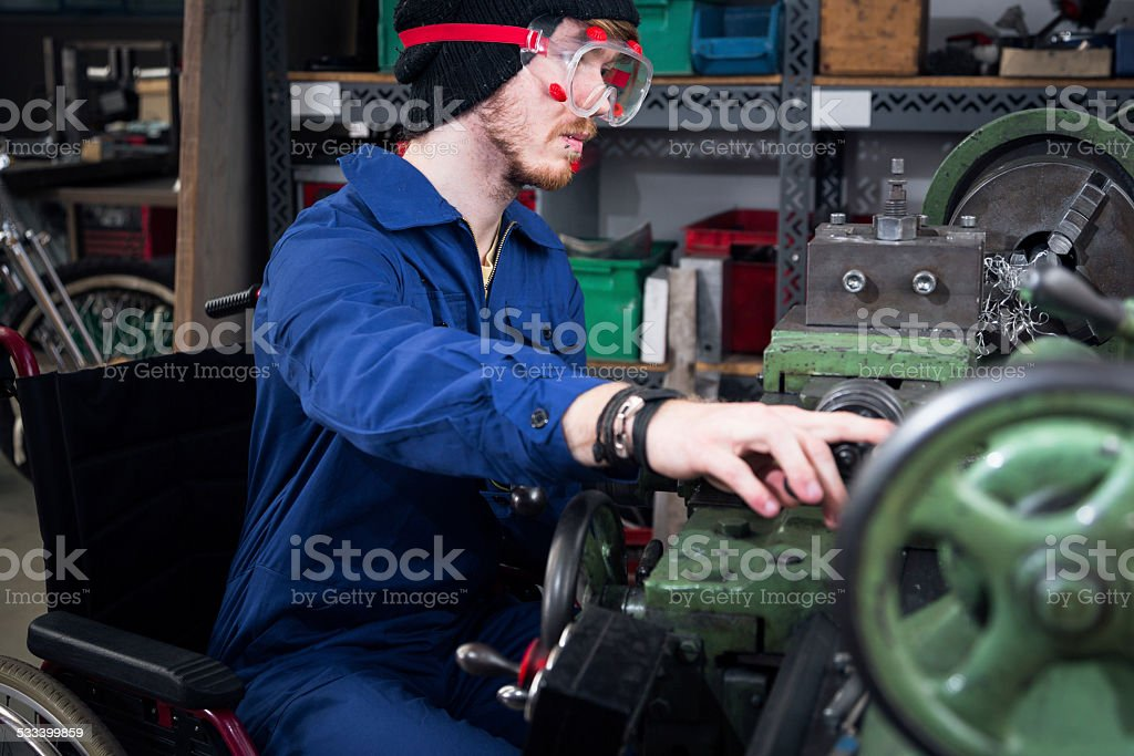 Junge Mechaniker/Auszubildende im Rollstuhl, der auf der Straße Drehmaschine – Foto