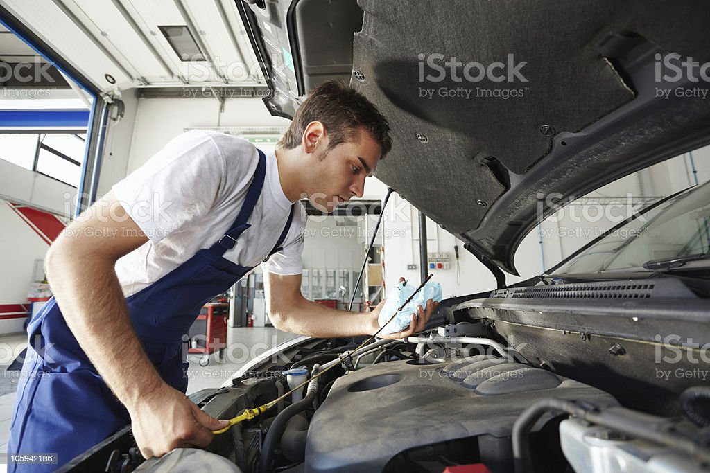 Young mechanic checking the oil level of a car stock photo