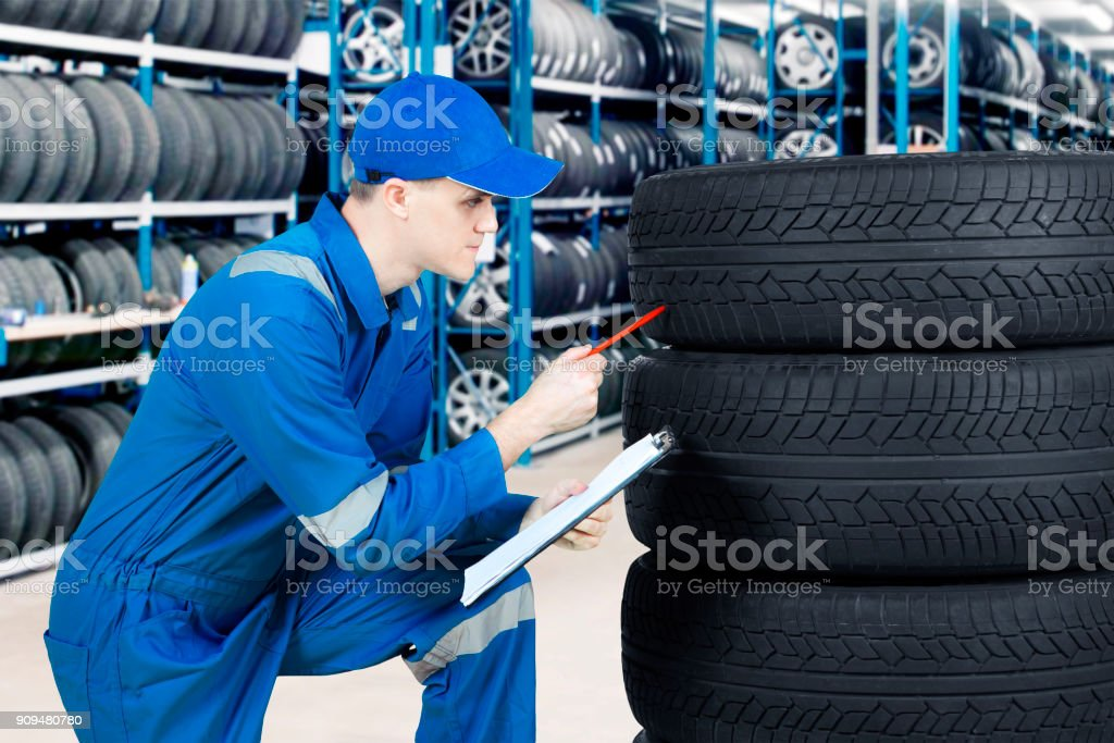 Young mechanic checking tyre in workshop royalty-free stock photo