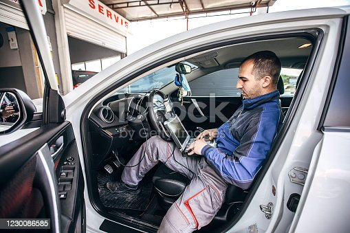 One young mechanic doing car diagnostic in auto repair shop.