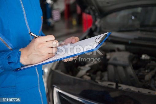 962888586 istock photo Young mechanic engineer taking a note and examining a vehicle 521457706
