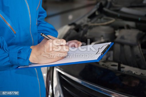 962888586 istock photo Young mechanic engineer taking a note and examining a vehicle 521457792