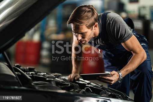 1137474295 istock photo Young mechanic examining broken car engine while using touchpad in auto  repair shop. 1191781527