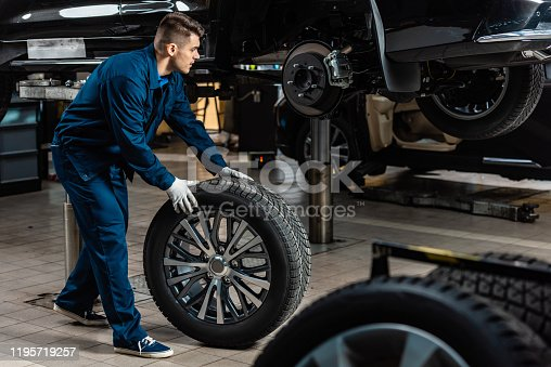 young mechanic holding car wheel near raised car in workshop