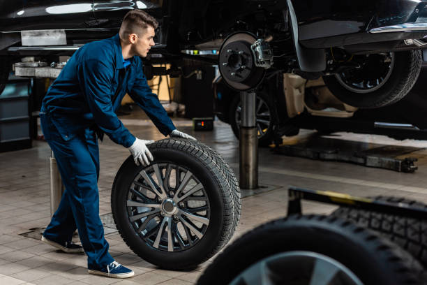 young mechanic holding car wheel near raised car in workshop stock photo