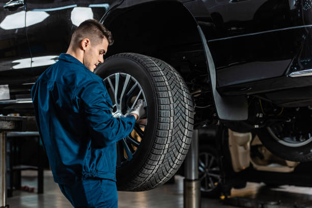 young mechanic installing wheel on raised car in workshop stock photo