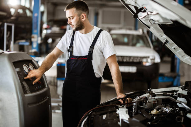 Young mechanic recharging car air-condition in auto repair shop. Young auto mechanic refueling car AC in a repair shop. car air conditioner stock pictures, royalty-free photos & images