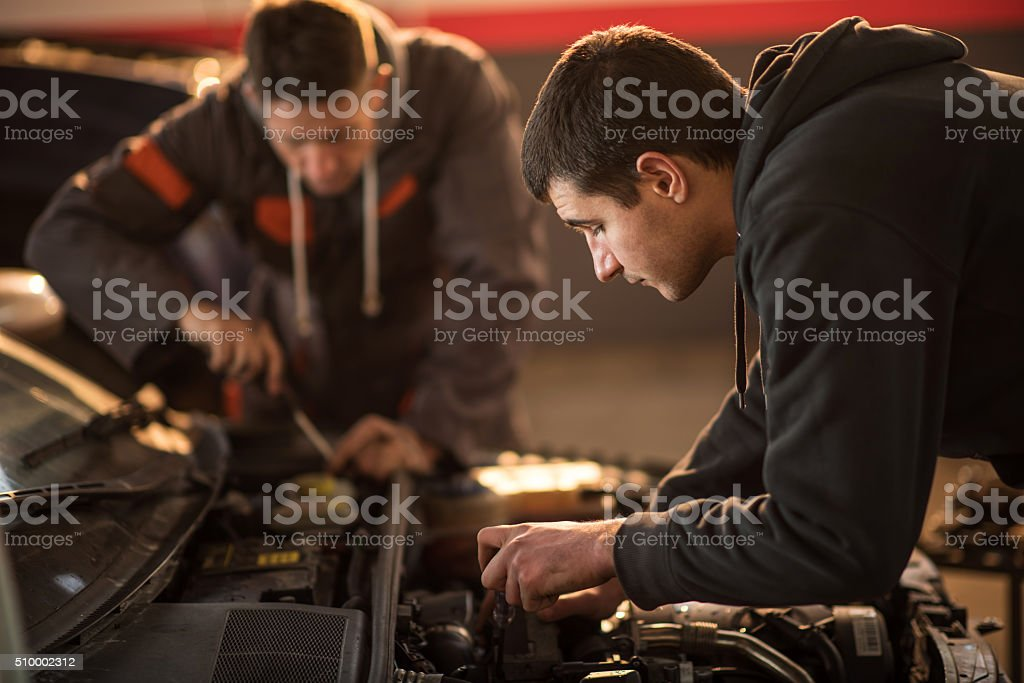 Young mechanic repairing a car in auto repair shop. stock photo