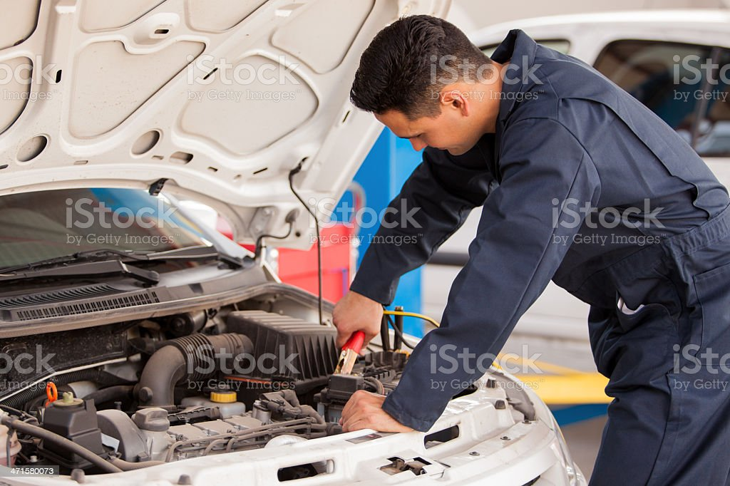 Young mechanic using jumper cables on a battery stock photo