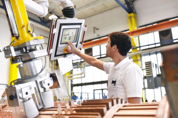 年輕的機械工程工作者操作機器為繞組銅線-製造變壓器在工廠 - 工業建築物 個照片及圖片檔