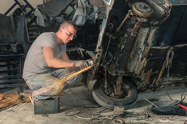 junge mechanische arbeiter reparieren einer alten oldtimer körper - autoschleifen stock-fotos und bilder