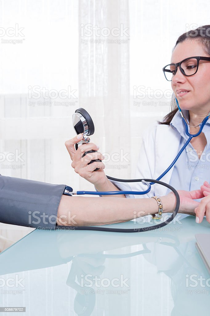 Young medic measuring patient blood pressure stock photo