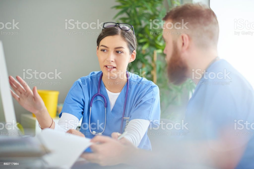 young medical professional discussing notes stock photo