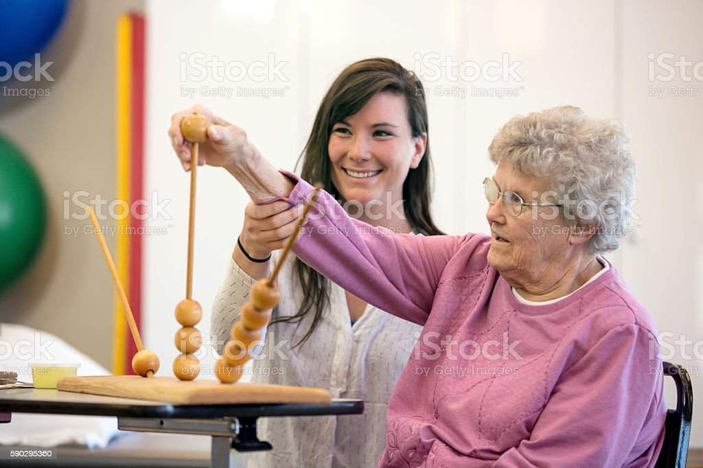 Young medical professional helping elderly woman royaltyfri bildbanksbilder