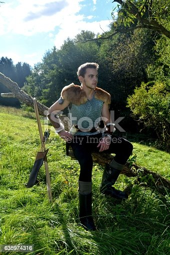 630040004istockphoto Young Medieval dressed man, sits on branch  and looks aside 635974316