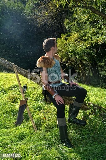 630040004istockphoto Young Medieval dressed man, sits on branch,  and looks backwards 635974120