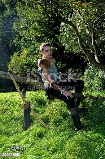 630040004istockphoto Young Medieval dressed man, sits on branch  and looks forwards 635974556