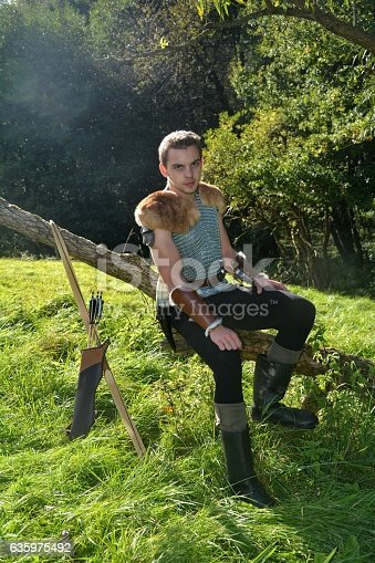630040004istockphoto Young Medieval dressed man, sits on branch  and looks forwards 635975492