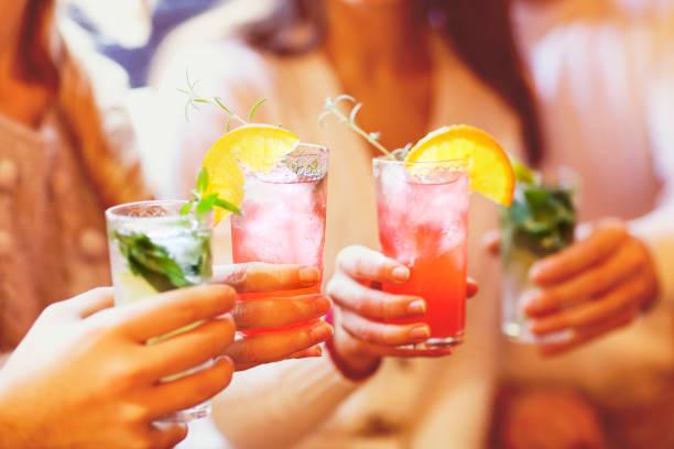 junge männer und frauen trinken cocktail party - alkoholfreies getränk stock-fotos und bilder