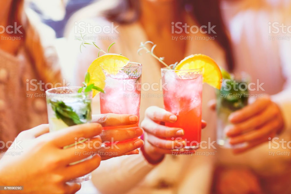 Young men and women drinking cocktail at party stock photo